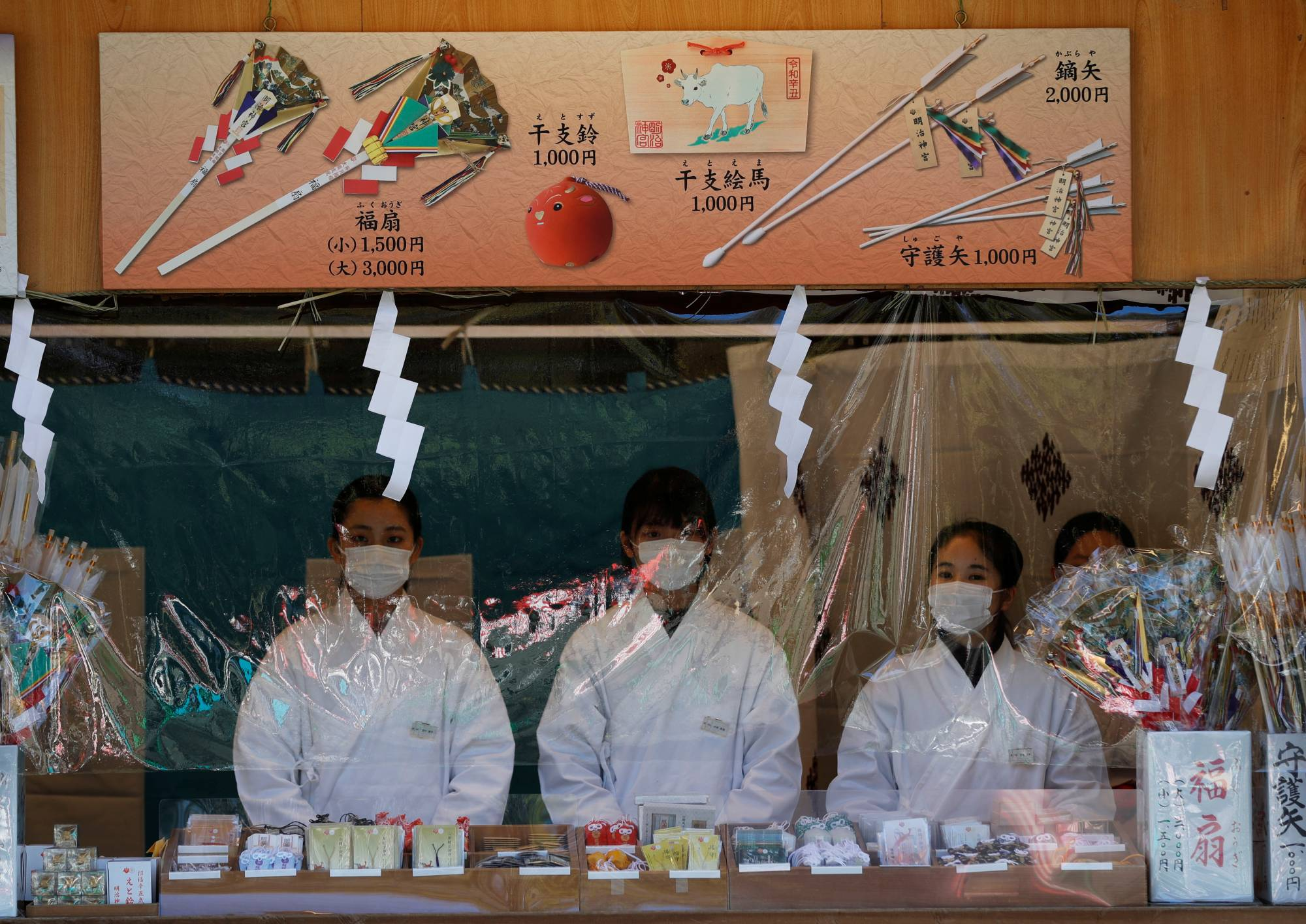Shinto priests wearing protective masks stand behind a plastic curtain on the new year's first day at the Meiji Shrine.   REUTERS