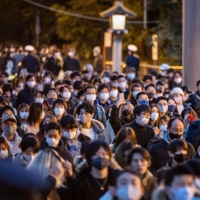 People line up to offer New Year's prayers at Meiji Shrine on Friday in Tokyo. | AFP-JIJI