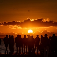 People gather at a beach near Chigasaki, in Kanagawa Prefecture, southwest of Tokyo, to watch the sunrise on New Year's Day. | AFP-JIJI