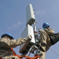 Workers install a 5G base station in Jiangsu Province in China in April 2020.  | KYODO