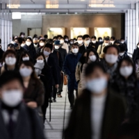 People walk through Shinjuku Station during the morning rush in Tokyo on Monday. Prime Minister Yoshihide Suga is considering a new state of emergency declaration for Tokyo and three neighboring prefectures amid a surge in COVID-19 cases. | AFP-JIJI