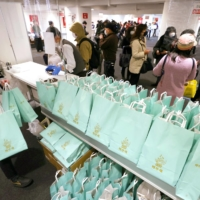 People buy New Year lucky bags at the Seibu department store in Tokyo's Ikebukuro district on Jan. 1. | KYODO
