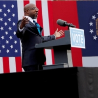 U.S. Senate candidate Rev. Raphael Warnock speaks before the arrival of U.S. President-elect Joe Biden to campaign on behalf of Jon Ossoff and himself ahead of their Tuesday runoff elections, during a drive-in campaign rally at Pullman Yard in Atlanta on Dec. 15, 2020. | REUTERS