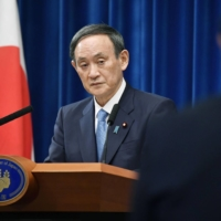 Prime Minister Yoshihide Suga speaks during an annual New Year's news conference Monday at the Prime Minister's Office in Tokyo. | KYODO