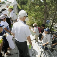People climb up the stairs to an expressway during a tsunami drill held in the coastal city of Iwanuma, Miyagi Prefecture, in September 2012. | KYODO