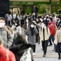 People walk near Shibuya Station in Tokyo on Monday morning. | KYODO
