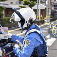Police officers call on people to drive safely during a campaign conducted in Takaishi, Osaka Prefecture, in September. | KYODO