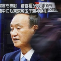 A screen in Tokyo shows Prime Minister Yoshihide Suga holding a news conference Monday, during which he mentioned that a state of emergency was under consideration. | KYODO