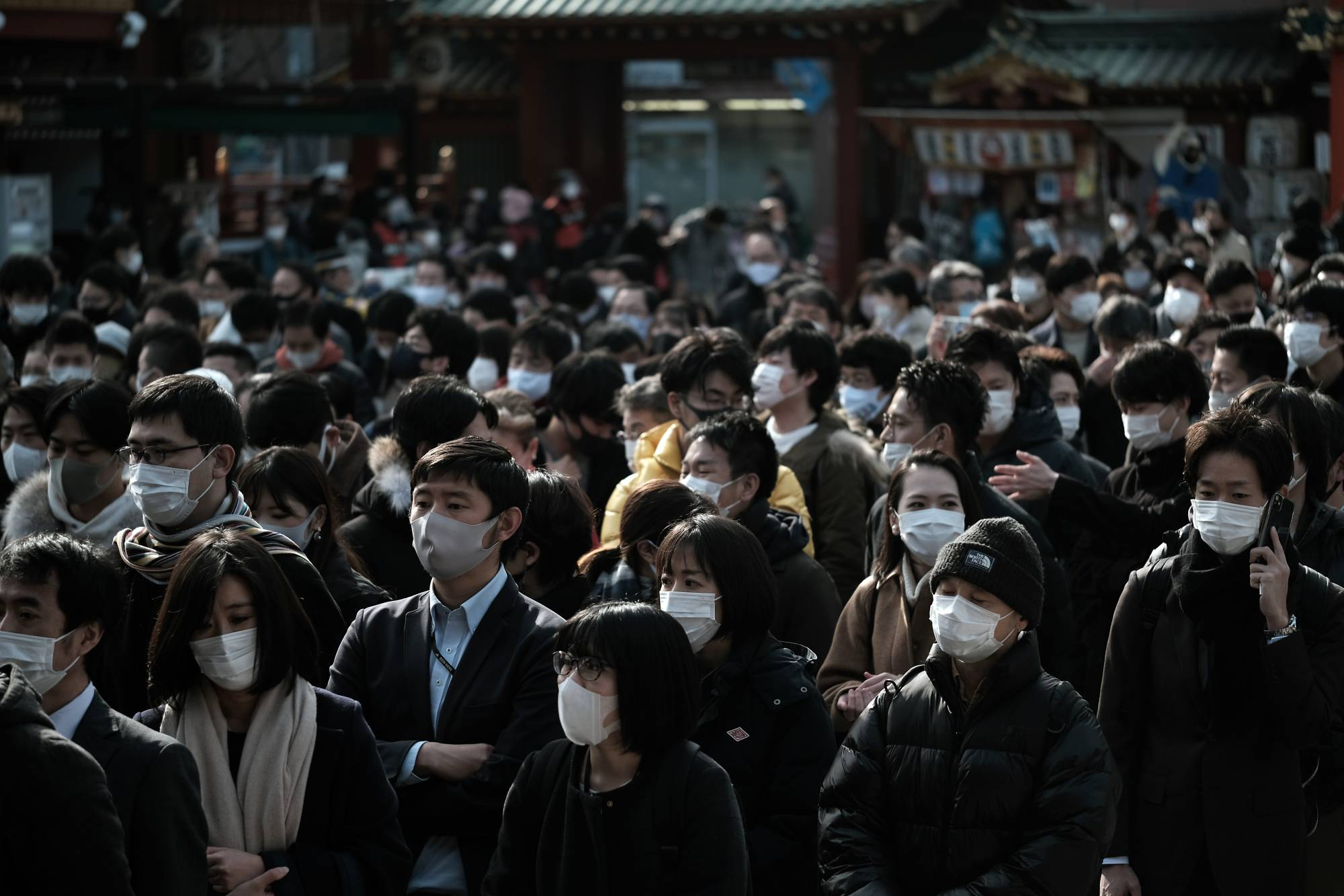 People wearing protective face masks as they line up to offer prayers on the first business day of the year at the Kanda Myojin shrine in Tokyo on Monday. | BLOOMBERG