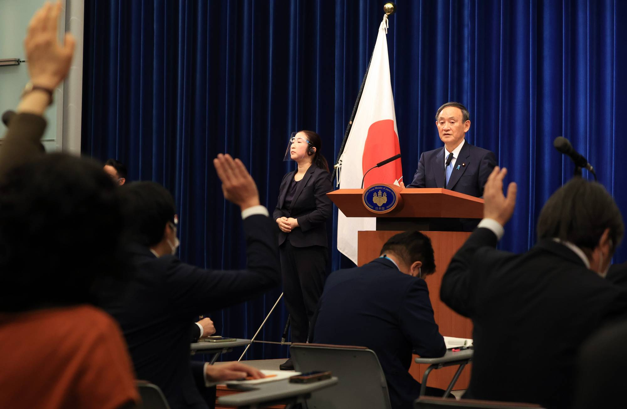 Journalists raise their hands to ask questions of Prime Minister Yoshihide Suga during a news conference at the Prime Minister's Office in Tokyo on Monday. | BLOOMBERG