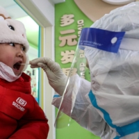 A child is tested for COVID-19 at a testing center set up at a primary school in Shenyang, Liaoning province, on Jan. 1. | AFP-JIJI