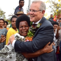 Australia's Prime Minister Scott Morrison greets local residents in Port Moresby, Papua New Guinea, in November 2018. Morrison's government has promised to supply its Pacific Island neighbors with COVID-19 vaccines in 2021 as part of a package aimed at achieving 'full immunization coverage' in the region. | REUTERS