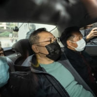 Benny Tai (center), a pro-democracy activist, arrives at the Ma On Shan police station after being arrested in Hong Kong on Wednesday. | BLOOMBERG