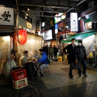 People enjoy drinking and dining at an izakaya-style pub amid the COVID-19 outbreak in Tokyo on Tuesday. | REUTERS