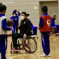 Yasuhiro Jimbo demonstrates the specialized equipment used for wheelchair basketball to students at Yokoshibahikari Junior High School in Chiba Prefecture during a December 2020 event hosted by the Nippon Foundation Paralympic Support Center. | KAZ NAGATSUKA