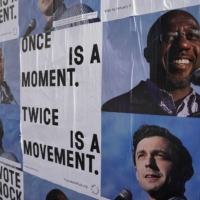 Campaign ads for Jon Ossoff and Raphael Warnock on a wall near the John Lewis mural the day after the U.S. Senate runoff elections in Atlanta, Georgia | REUTERS