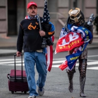 A supporter of U.S. President Donald Trump wears a costume from the movie 'Predator' while walking on a downtown Washington street as Trump backers from around the country rallied in the U.S. capital to protest the upcoming Electoral College certification of Joe Biden as president on Wednesday. | AFP-JIJI