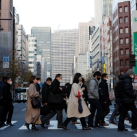 Pedestrians cross a street during peak commuting time at a business district in Tokyo on Thursday. | REUTERS