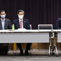 Front, from left: Health minister Norihisa Tamura, Shigeru Omi, who heads a new government subcommittee on COVID-19 measures, and economic revitalization minister Yasutoshi Nishimura discuss the second state of emergency at a meeting in Tokyo on Thursday. | KYODO