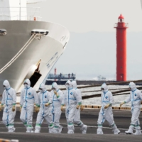 Workers wear protective gear to protect them against the COVID-19 virus near the cruise ship Diamond Princess at Daikoku Pier Cruise Terminal in Yokohama last February. More than 700 of the 3,711 people on board the ship became infected with the virus, with 14 deaths being reported.