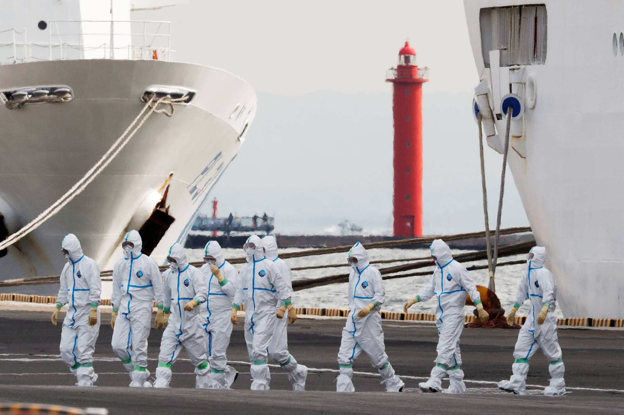 Workers wear protective gear to protect them against the COVID-19 virus near the cruise ship Diamond Princess at Daikoku Pier Cruise Terminal in Yokohama last February. More than 700 of the 3,711 people on board the ship became infected with the virus, with 14 deaths being reported. |  REUTERS