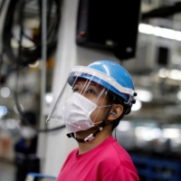A worker at an automobile assembly line at the Mitsubishi Fuso Truck and Bus Corp. factory in Kawasaki takes protective measures against COVID-19. | REUTERS