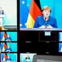 German Chancellor Angela Merkel is seen on a monitor as she addresses the Christian Social Union Bundestag parliamentary group's winter meeting in Berlin on Thursday. | POOL / VIA REUTERS