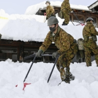 Self-Defense Forces personnel remove snow from the roof of an elementary school in Yokote, Akita Prefecture, on Thursday. | KYODO
