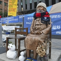 A statue symbolizing 'comfort women' who suffered under Japan's military brothel system before and during World War II stands in front of the Japanese Embassy in Seoul. | KYODO