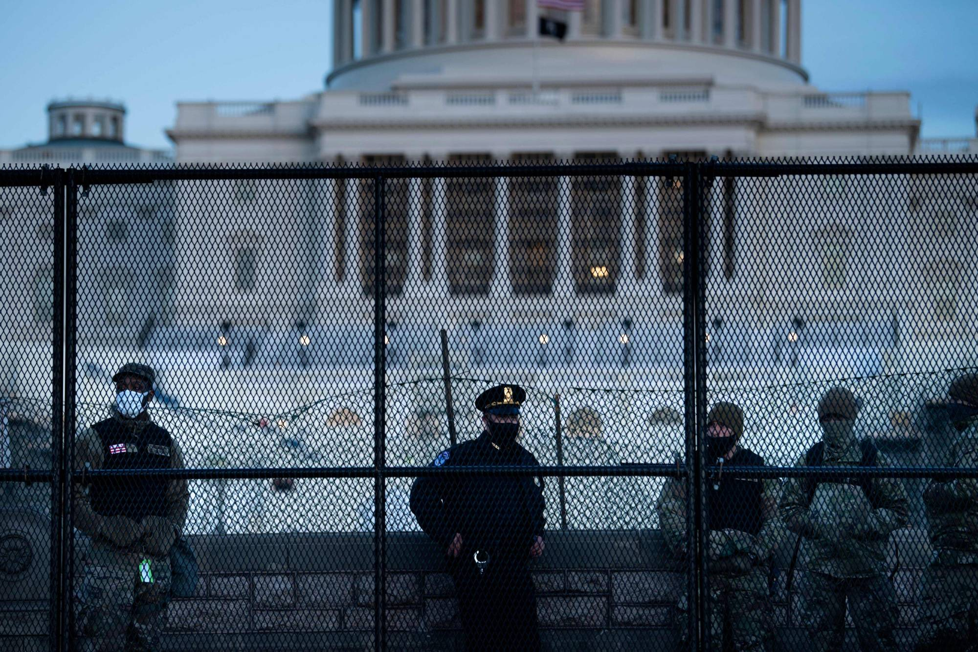 A Capitol Police officer stands with members of the National Guard behind a crowd control fence surrounding Capitol Hill in Washington on Thursday, a day after a pro-Donald Trump mob broke into the U.S. Capitol. | AFP-JIJI