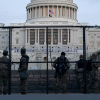 Members of the National Guard stand behind security fencing at the U.S. Capitol in Washington on Thursday.  | BLOOMBERG