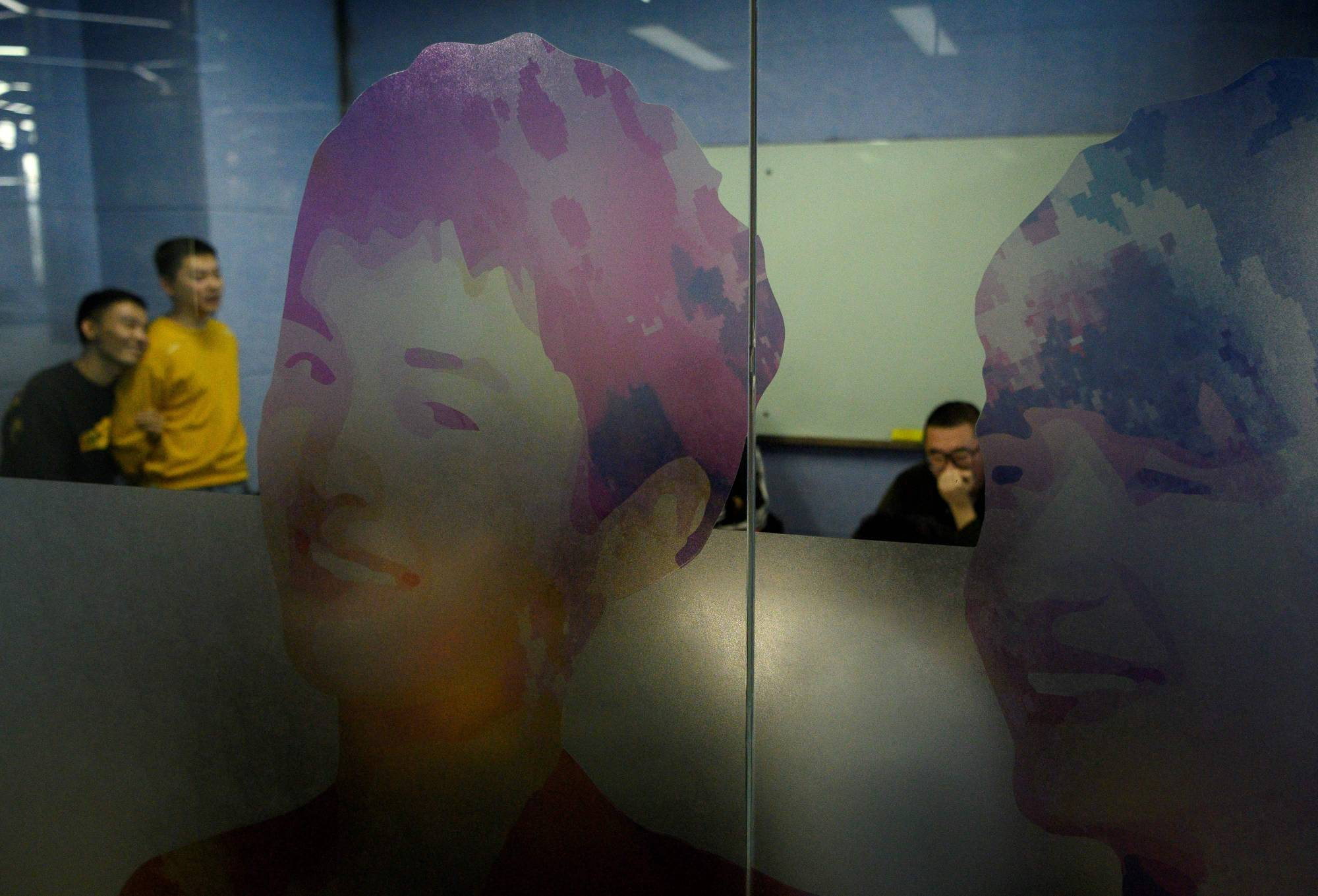 Employees work at the BlueCity headquarters in Beijing in December. The sunlit, crowded offices are filled with rainbow-hued unicorn mascots, gender-neutral toilets and photos of CEO Ma Baoli's meetings with dignitaries including China's premier Li Keqiang. | AFP-JIJI