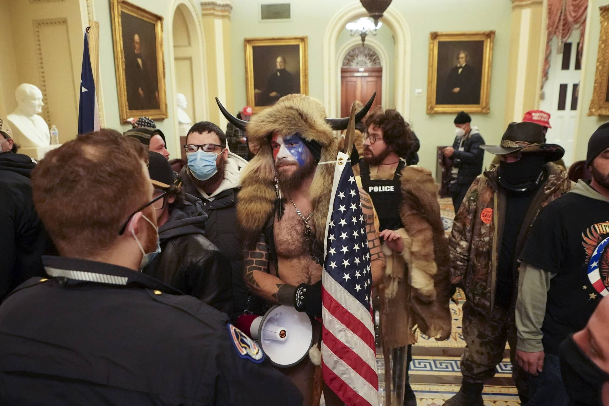 Rioters who swarmed the U.S. Capitol confront Capitol Police officers in the building, in Washington, on Wednesday. As people rushed inside, there was a strange mix of confusion and excitement, and the almost complete lack of police presence in the beginning amplified the feeling of lawlessness. | ERIN SCHAFF / THE NEW YORK TIMES