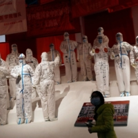 A visitor attends an exhibition on the fight against the coronavirus pandemic, at Wuhan Parlor Convention Center, which previously served as a makeshift hospital for COVID-19 patients in Wuhan, China, on Dec. 31. | REUTERS