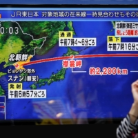 A passerby looks at a TV screen in Tokyo reporting news about a North Korean missile launch in September 2017. North Korean leader Kim Jong Un has vowed to develop more advanced nuclear weapons and missiles, state-run media said Saturday. | REUTERS