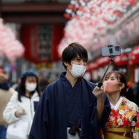 A man in kimono holds a selfie stick in the Asakusa district of Tokyo on Friday. | REUTERS
