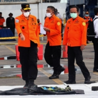 Rescue workers carry debris off a search and rescue ship at the port in Jakarta on Sunday during search operations for Sriwijaya Air flight SJY182, which crashed after takeoff from Jakarta on Saturday.  | AFP-JIJI