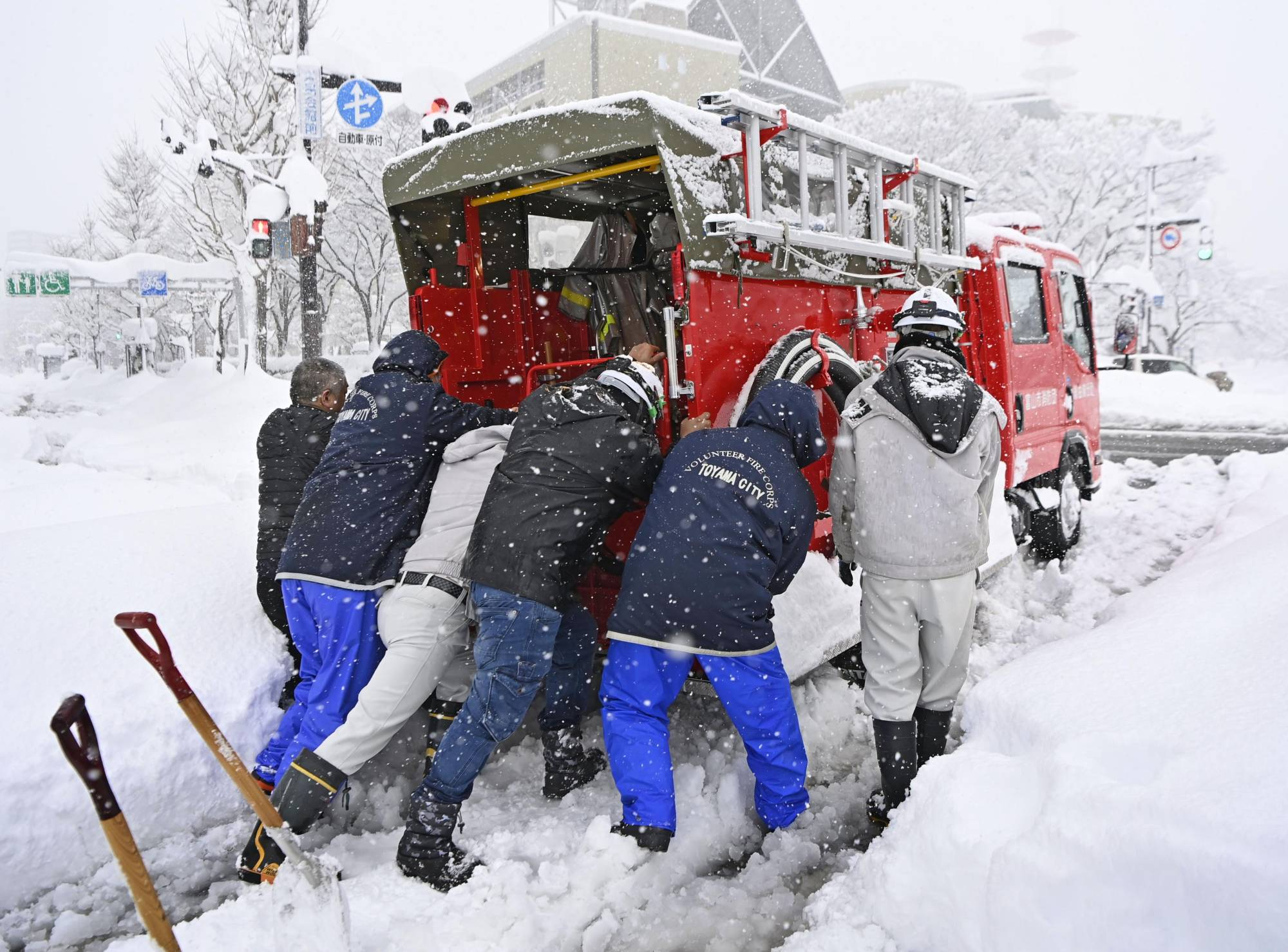 People push a firetruck stranded in snow in Toyama on Saturday. | KYODO