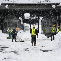 Workers clear the snow in front of Toyama Station in the city of Toyama on Sunday. | KYODO
