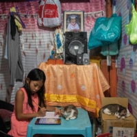 Nhieshalyn Galicia, 8, works on a school assignment at her home in Manila.  | REUTERS