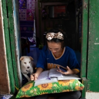 Annie Sabino, 16, completes her school work while tending to her family's sidewalk eatery beside their home in Manila. | REUTERS