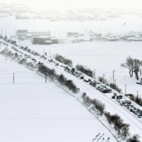 Hundreds of vehicles are stranded due to heavy snow on the Hokuriku Expressway in Fukui Prefecture on Sunday. | KYODO