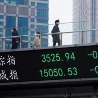 People walk on an overpass with an electronic board showing Shanghai and Shenzhen stock indexes in Shanghai on Wednesday.  | REUTERS