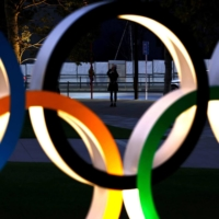 A woman takes pictures of Olympic rings in Tokyo on Friday. In a new poll, 35.3% of people in Japan called for the cancellation of the Tokyo Games, while 44.8% said the event should be put off again. | AFP-JIJI