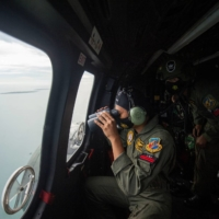An Indonesian Air Force member looks through the window of a helicopter during an aerial search for the Sriwijaya Air SJ182, which crashed into the sea near Jakarta, on Sunday. | ANTARA FOTO / VIA REUTERS