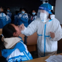 A medical worker collects a swab sample from a middle school student during mass nucleic acid testing following a recent coronavirus outbreak in Xingtai, Hebei province, China, on Wednesday. | CHINA DAILY / VIA REUTERS