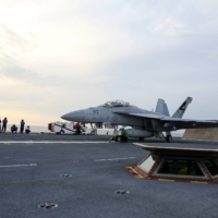 A U.S. Navy sailor guides an F/A-18F Super Hornet onto the electromagnetic launching system, which replaces the steam-piston catapult, on the aircraft carrier USS Gerald R. Ford in the Atlantic Ocean in July 2017. | U.S. NAVY / VIA REUTERS