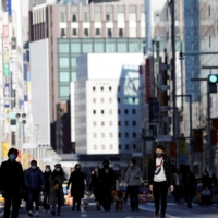 Pedestrians wearing protective masks make their way through Tokyo's Ginza shopping district, which closed to cars on Sunday. | REUTERS