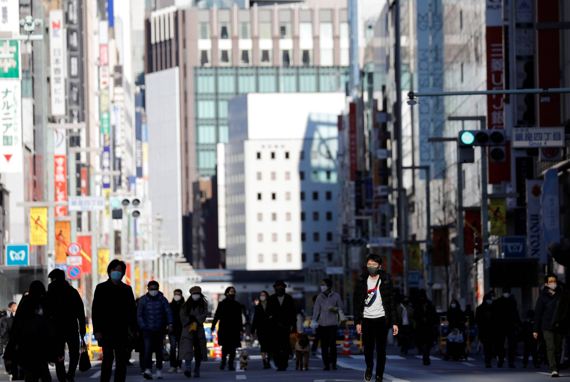Pedestrians wearing protective masks make their way through Tokyo's Ginza shopping district, which closed to cars on Sunday.   REUTERS