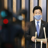 Economic revitalization minister Yasutoshi Nishimura, who oversees the government's coronavirus response, speaks with reporters after an online meeting with three governors from the Kansai region on Saturday in Tokyo. | KYODO